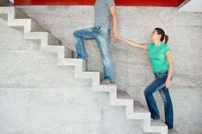 A man leading a woman upward
