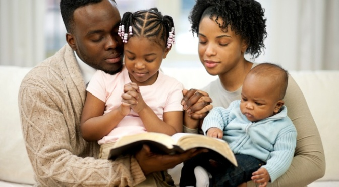A family praying and reading the Bible