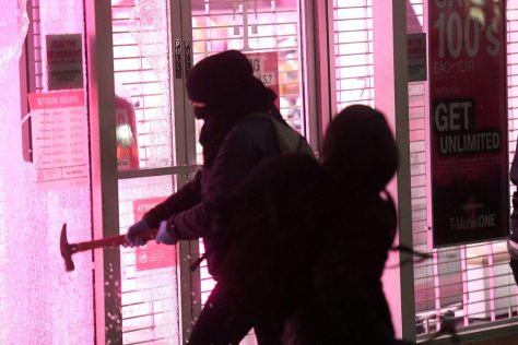 Rioters smash windows at a T-Mobile store during a protest against campus speaker