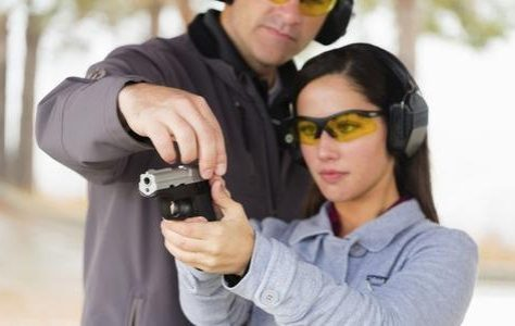 Man teaching woman proper marksmanship