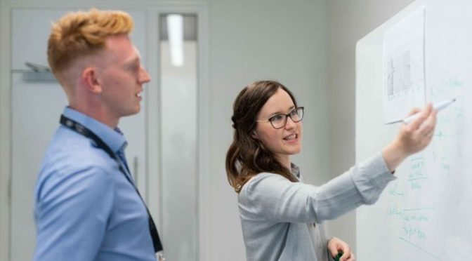 Woman Showing Her Work On Whiteboard